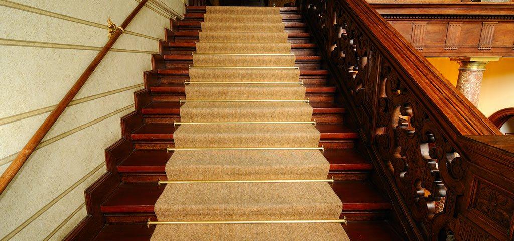 Treppenaufgang mit Sisalläufer und Messingstangen
